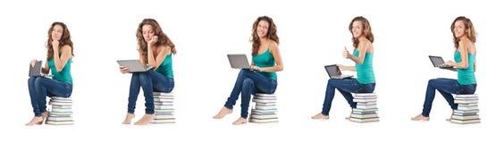 El estudiante con el netbook que se sienta en los libros Fotografía de archivo libre de regalías