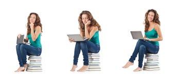 El estudiante con el netbook que se sienta en los libros Foto de archivo libre de regalías