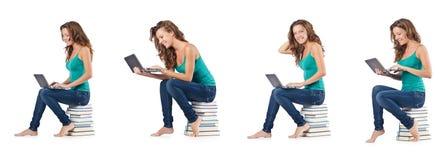 El estudiante con el netbook que se sienta en los libros Foto de archivo
