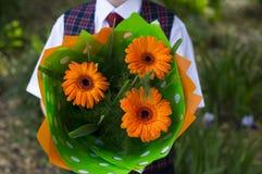 El estudiante con las flores, un cierre de la escuela para arriba Foto de archivo
