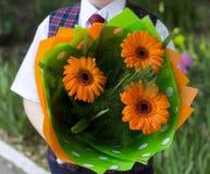 El estudiante con las flores, un cierre de la escuela para arriba, flores en el centro Imagenes de archivo
