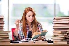 El estudiante con las pilas de libros que se preparan para los exámenes Fotografía de archivo