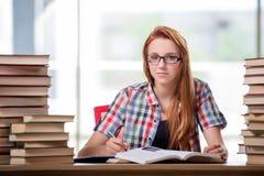 El estudiante con las pilas de libros que se preparan para los exámenes Fotos de archivo