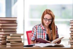 El estudiante con las pilas de libros que se preparan para los exámenes Foto de archivo libre de regalías