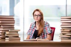 El estudiante con las pilas de libros que se preparan para los exámenes Imágenes de archivo libres de regalías