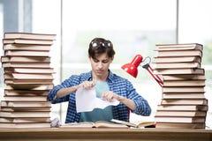 El estudiante con las porciones de libros que se preparan para los exámenes Imágenes de archivo libres de regalías