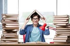 El estudiante con las porciones de libros que se preparan para los exámenes Imagen de archivo