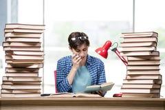 El estudiante con las porciones de libros que se preparan para los exámenes Foto de archivo