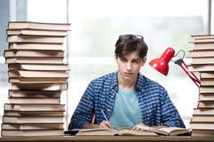 El estudiante con las porciones de libros que se preparan para los exámenes Fotos de archivo