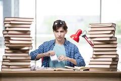 El estudiante con las porciones de libros que se preparan para los exámenes Fotografía de archivo