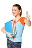 El estudiante con sus libros a disposición muestra thumb-up Imagen de archivo libre de regalías
