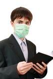 El estudiante con un libro en la máscara médica Imágenes de archivo libres de regalías