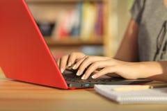 El estudiante da la escritura en un ordenador portátil rojo en casa Imagen de archivo
