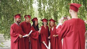 El estudiante de graduación está registrando el vídeo de sus amigos en los vestidos que celebran los diplomas, las manos que agit almacen de video