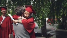 El estudiante de graduación feliz de la hija está abrazando a su hombre barbudo del padre cariñoso y riendo, la muchacha está sos metrajes