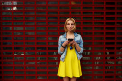 El estudiante de la chica joven en un vestido amarillo brillante que se coloca cerca de la tienda, escribe un mensaje a un amigo Fotografía de archivo