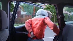 el estudiante de la Elemental-escuela va a la escuela El muchacho fuera del coche y el agitar a sus padres almacen de metraje de vídeo