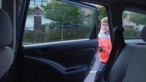 el estudiante de la Elemental-escuela va a la escuela El muchacho fuera del coche y el agitar a sus padres metrajes