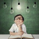 El estudiante de la escuela primaria se sienta debajo de bombilla Imagen de archivo libre de regalías
