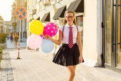 El estudiante de la High School secundaria del adolescente de la muchacha con los globos, en uniforme escolar con los vidrios va  Fotografía de archivo
