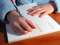 El estudiante de las manos escribe Imagen de archivo