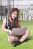 El estudiante de moda utiliza el ordenador portátil en el parque Foto de archivo