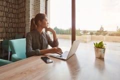 El estudiante de mujer japonés está pensando en algo durante rotura entre el aprendizaje en Internet vía el red-libro portátil, foto de archivo