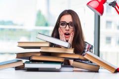 El estudiante de mujer joven con muchos libros Imagen de archivo libre de regalías