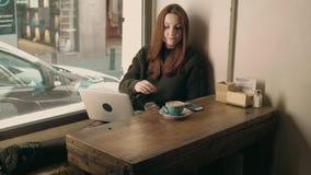 El estudiante de mujer joven trabaja remotamente en el café metrajes