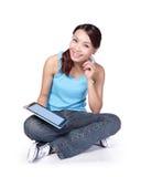 El estudiante de mujer se sienta y con la tableta digital Imagen de archivo