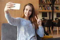 El estudiante de mujer sonriente que se sienta en biblioteca hace el selfie Imágenes de archivo libres de regalías