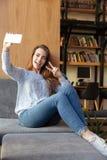 El estudiante de mujer sonriente que se sienta en biblioteca hace el selfie Imagen de archivo libre de regalías