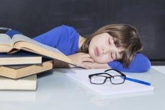 El estudiante de trabajo duro magnífico joven se cayó dormido en una pila de sus libros mientras que estudiaba fotos de archivo libres de regalías