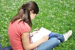 El estudiante de Whiteyoung aprende en un parque Foto de archivo libre de regalías