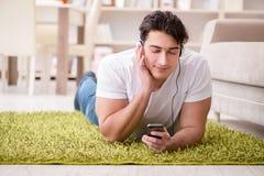 El estudiante del hombre joven que escucha la música en casa Fotografía de archivo libre de regalías