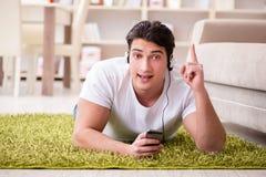 El estudiante del hombre joven que escucha la música en casa Imagenes de archivo