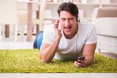 El estudiante del hombre joven que escucha la música en casa Imágenes de archivo libres de regalías