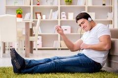 El estudiante del hombre joven que escucha la música en casa Foto de archivo