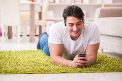 El estudiante del hombre joven que escucha la música en casa Imagen de archivo libre de regalías