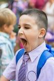 El estudiante del niño pequeño está bostezando temprano por la mañana fotografía de archivo libre de regalías