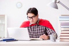 El estudiante del superhéroe con un ordenador portátil que estudia la preparación para los exámenes Foto de archivo libre de regalías