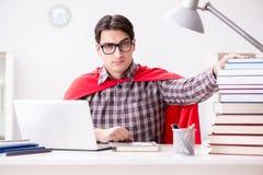 El estudiante del superhéroe con un ordenador portátil que estudia la preparación para los exámenes Imágenes de archivo libres de regalías