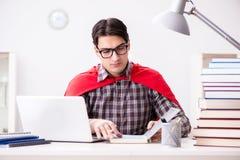 El estudiante del superhéroe con un ordenador portátil que estudia la preparación para los exámenes Fotos de archivo