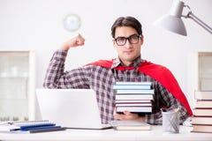 El estudiante del superhéroe con un ordenador portátil que estudia la preparación para los exámenes Imagenes de archivo