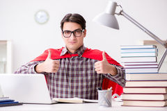 El estudiante del superhéroe con un ordenador portátil que estudia la preparación para los exámenes Fotografía de archivo libre de regalías