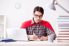 El estudiante del superhéroe con un ordenador portátil que estudia la preparación para los exámenes Fotografía de archivo