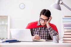 El estudiante del superhéroe con un ordenador portátil que estudia la preparación para los exámenes Imagen de archivo