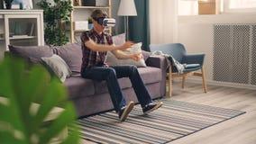 El estudiante despreocupado está jugando al juego con los vidrios de la realidad virtual que conducen las carreras de coches que  metrajes