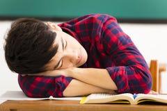 El estudiante duerme en el escritorio en sala de clase Imagenes de archivo