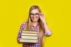 El estudiante elegante joven sonriente se está colocando con los libros en fondo amarillo en vidrios y equipo brillante casual Imagenes de archivo
